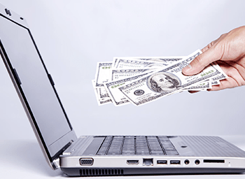 Hand Holding Cash Infront of Laptop