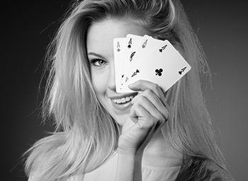 woman is holding 4 aces smiling