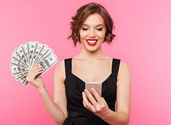 woman in dress holding phone and handful of dollar notes