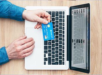 man using credit card to deposit money in laptop