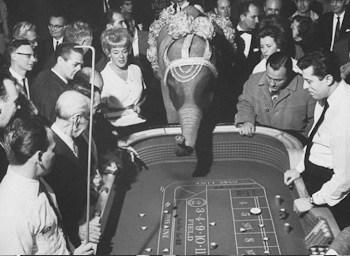 black & white image of people gathered around a craps table
