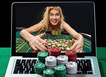 Happy woman at roulette table collecting chips through a laptop screen
