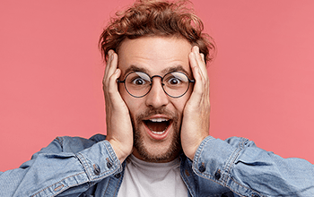 male in glasses holding his head in surprise