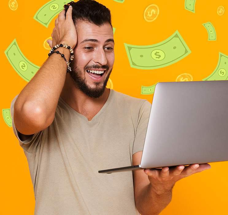dark haired video poker male winner happily staring at laptop screen