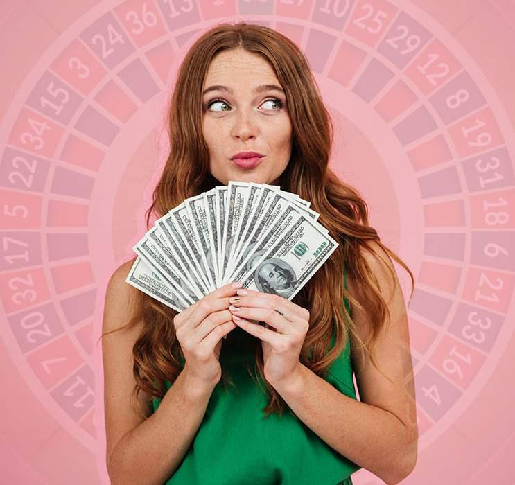 young video poker female winner holding a hand of dollar notes