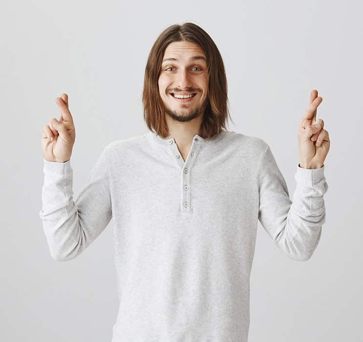 video poker male winner in grey clothes crossing fingers
