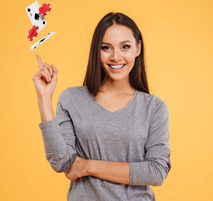 Online Blackjack female winner pointing her finger with cards flying around