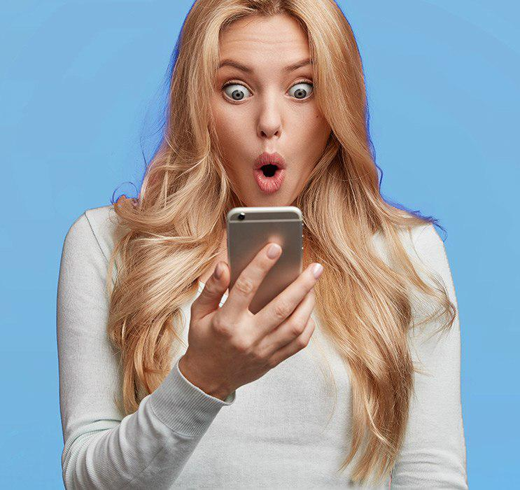 Blonde female looking into phone with surprised expression on face